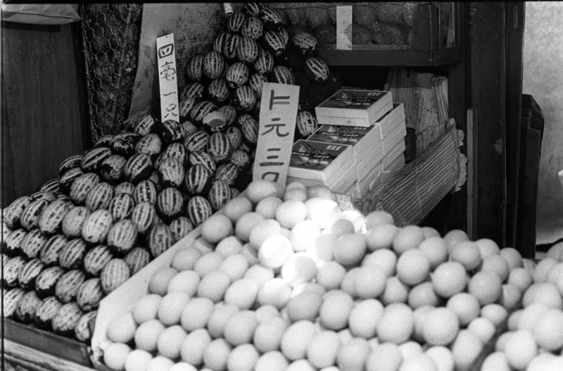 Preserved duck eggs (left) and ordinary eggs in a stall. The preserved duck eggs are forty cents each while the ordinary eggs are $1.20 for three.