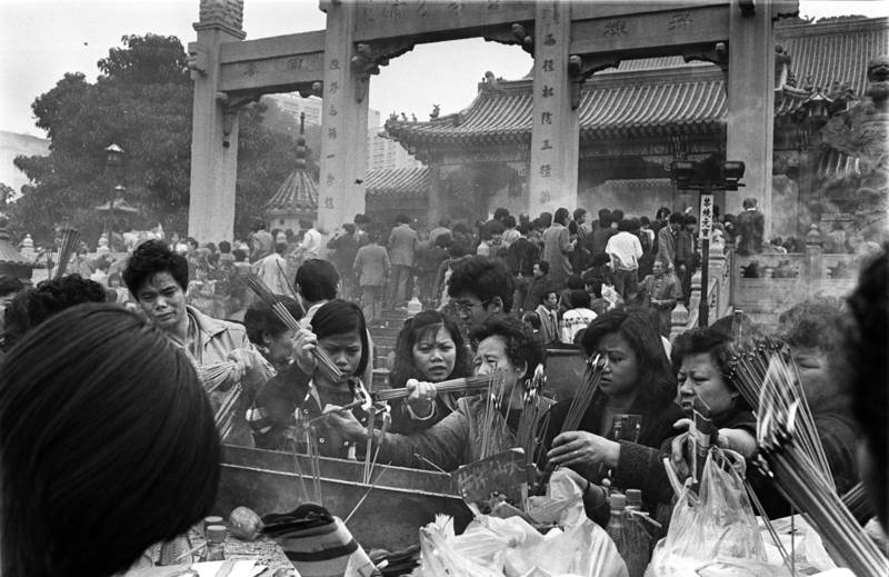 These women struggle to light their joss sticks in Wong Tai Sin Temple, Kowloon. They hope that Wong Tai Sin will bring them and their families fortune and good health.