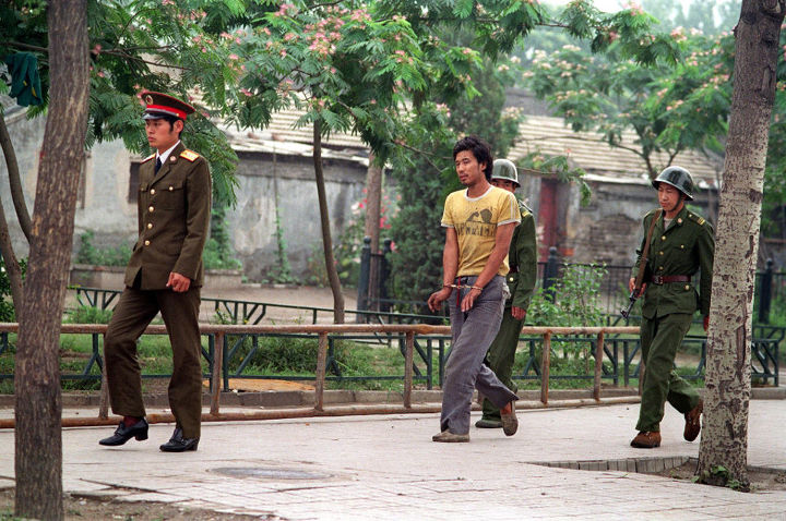 Picture dated 14 June 1989 shows a handcuffed man being led by Chinese soldiers on a street in Beijing as police and soldiers keep searching people involved in April-June pro-democracy protests. AFP